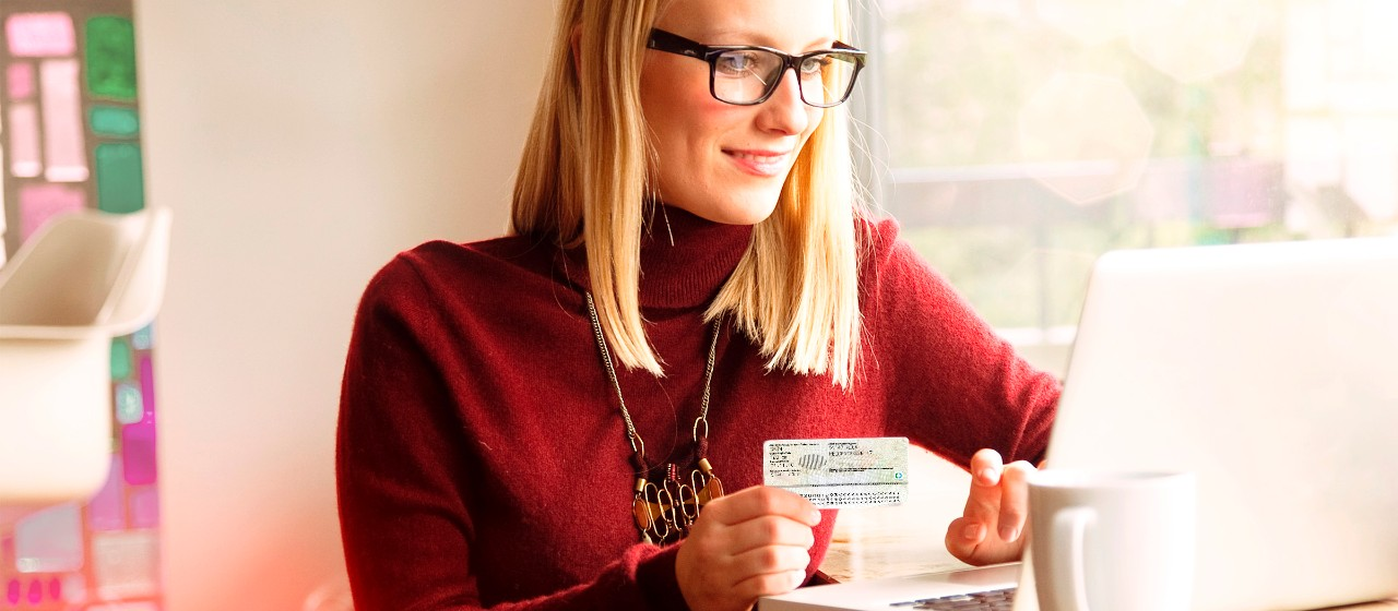 Frau mit Personalausweis am Laptop